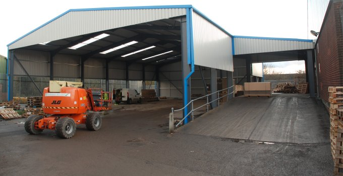 Wide entrance storage and loading bay showing space available with a steel-framed building