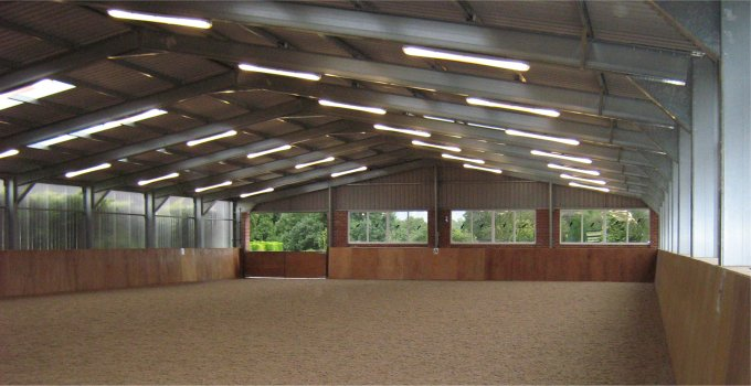 Interior view of steel-framed riding arena with windows providing lots of light