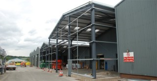 Steel building in construction showing the portal frame and cladding